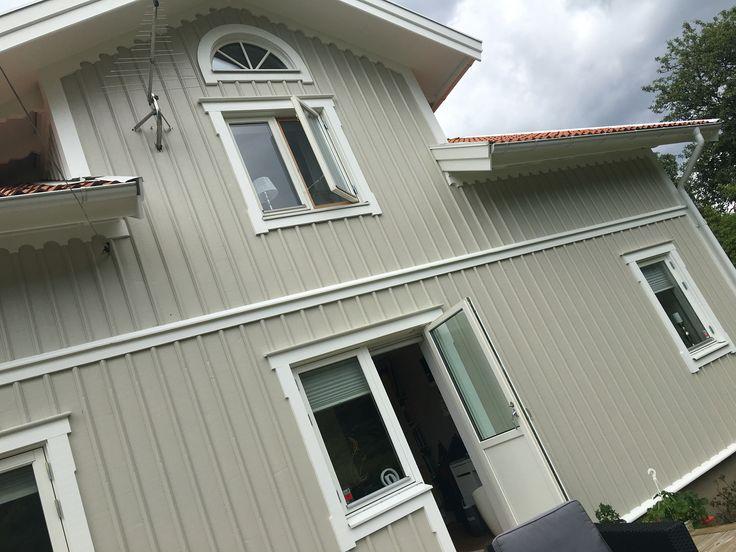 Vår husfasad målad i Jotuns Blek Sand med vita detaljer i Jotuns Lätthet