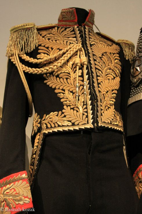 A black wool jacket with tails, featuring extensive gold bullion embroidery, red collar, cuffs and epaulets. Together with a pair of black wool pants with golden accented outer leg seams and interior label from Bermans and Nathans costumers of London.