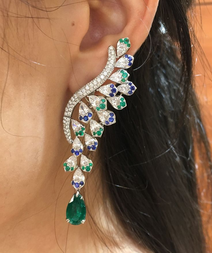 These emerald, sapphire and diamond earrings by Avakian combines high-quality stones with unusual cuts and a striking design. Entirely pavéd in diamonds, a sparkling curve gives way to feathers of blue and green. There is a matching ring and necklace.