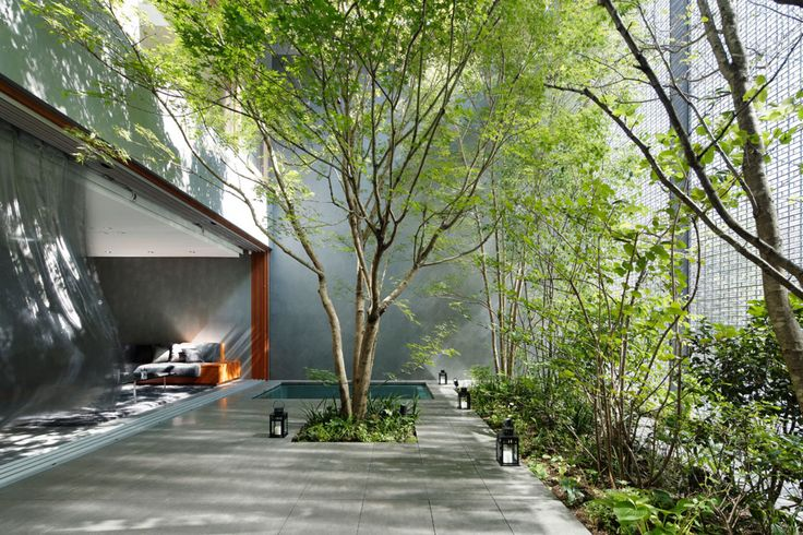This house is sited among tall buildings in downtown Hiroshima, overlooking a street with many passing cars and trams. To obtain privacy and tranquility in these surroundings, we placed a garden and optical glass façade on the street side of the house....