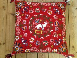 The Lammet med Korsfanan cushion. Traditional Swedish handicraft from Scania province (Skåne) with wool embroideries on wool fabric. The Swedish National Crafts Association, the Skåne province department. Cushions like those were used to sit on when went with horse carriage, for example to church. Nowadays embroidered and used as interior cushions.