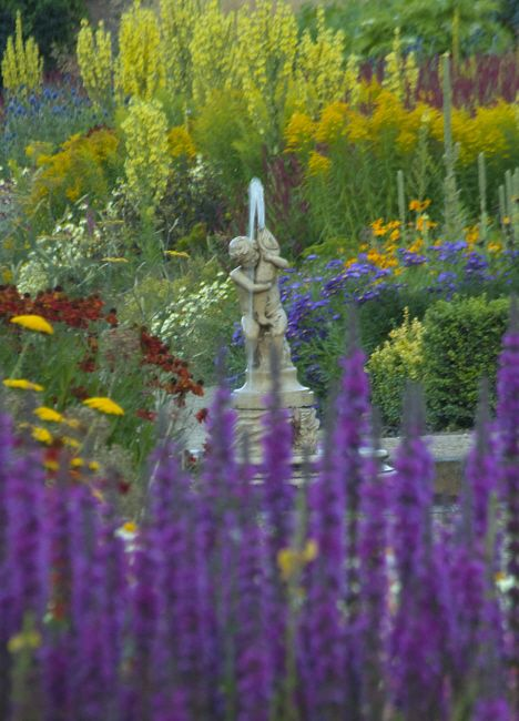 Helmsley Walled Garden - fountain amidst hot summer border by Jacky Hobbs