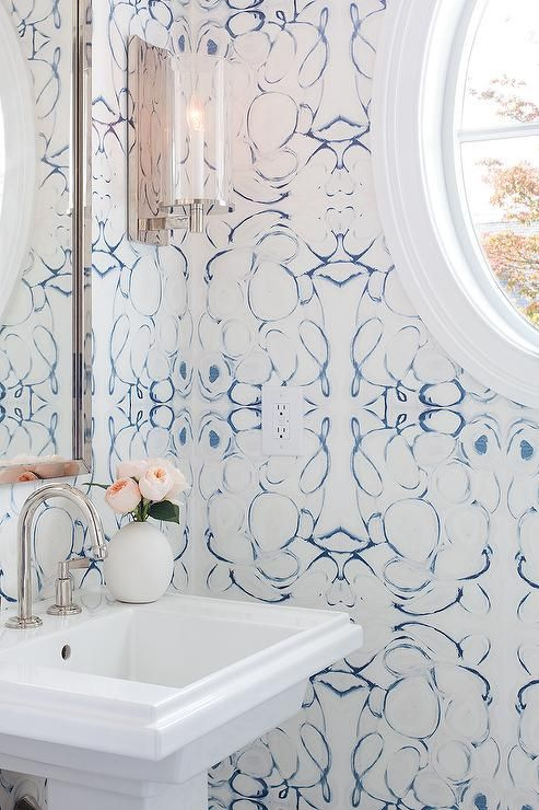 Lindsay Cowles Wallpaper line the walls of a blue powder room accented with  a polished nickel mirror and a white pedestal sink fitted with a polished  nickel ...