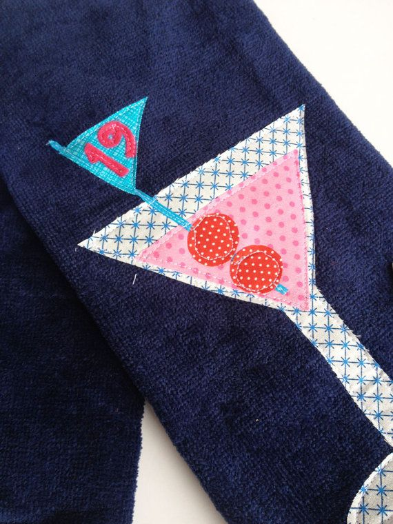 19th Hole Martini Golf Towel This navy blue golf towel has been appliqued with a pink martini dressed in designers fabrics. Perfect for the golfer who love the 19th hole. Applique is finished with the kakabaka signature white top stitch. Edges are designed to fray over the life of the