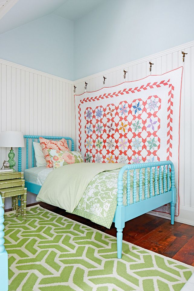 Cottage bedroom with turquoise Jenny Lind beds and quilt hanging from wall hooks Designed by Sarah Richardson.