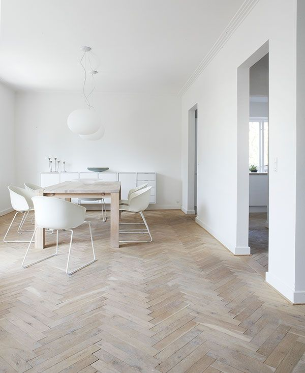 Dining room: wooden herringbone floor, white walls, wooden table, white dining chairs, white ball pendant lights