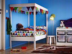 Vit säng med sänghimmel och påslakanset med triangelmönster i glada färger