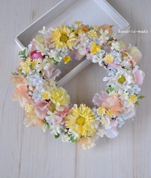 リースサイズ(縦・横・高さ 約 ㎝)26/27/7リース土台:ナチュラル素材 直径約20センチ リース素材:アーティフィシャルフラワ-(造花):スイトピー・デージー・スノーボール・アネモネ・バラ・ビオラ・ユーカリ、など。その他:リボンモチーフひらひらとした 花びらの花を たくさんあつめて ことしの春の景色を まるいリースにしました黄色のガーベラのようなデージー、小さな黄色のデージ-、白いアネモネ、オレンジ、ピンク、白いスイトピー、淡い水色、そして白にピンクの混じるスノーボールいろいろな花の表情を お楽しみいただけますように・・・季節の彩りに、お祝い、ウェディングシーン、ありがとうのきもちをこめた贈り物にも。リーストップに下げ用の紐がついています。イメージを損なわない程度に、お写真の状態に多少の資材を加えることがあります。***ご一読下さい******1)撮影の影響で、実際の色味と多少異なる場合がありますことをご容赦下さい。2)写真に写っています撮影用小物は販売の対象ではありません。アーティフィシャルフラワーについてポリエステルの布等でできている造花です。ホコリ...