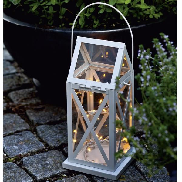Cream Lantern with 24 String Lights   Battery operated cream lantern with 24 LED lights with timer function. Batteries not included (require 3xAA). Light up your garden or terrace with cosy lanterns. There is no hassle with wind blowing out the light and no dependency on plugs, making you free to place the lanterns anywhere.           Width: 13,5cm, Depth: 13,5cm, Height: 35cm     PLEASE NOTE: Current lead time is 3-4 workingdays on this item. Thank you.