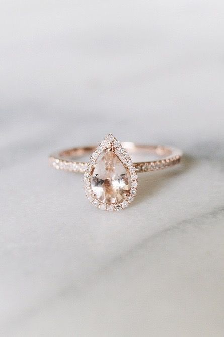 A Pear Shaped Diamond Engagement Ring With Halo Diamonds Sits On A Marble Table.