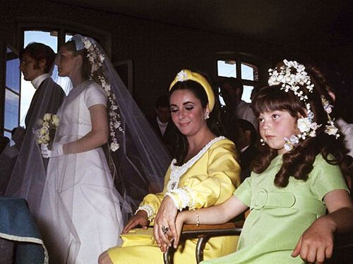 Elizabeth Taylor holding hands with her daughter Maria at her hairdresser's wedding.