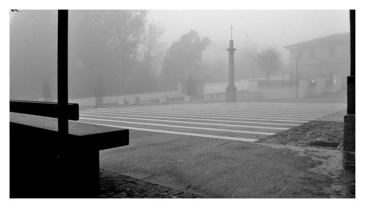 Il rettangolo di una moderna scacchiera, la seduta rettilinea in pietra,  l'antica stele in pietra arenaria con la croce e il grande albero, si rappresentano sullo sfondo della facciata neoclassica in una sorta di composizione metafisica dello spazio.