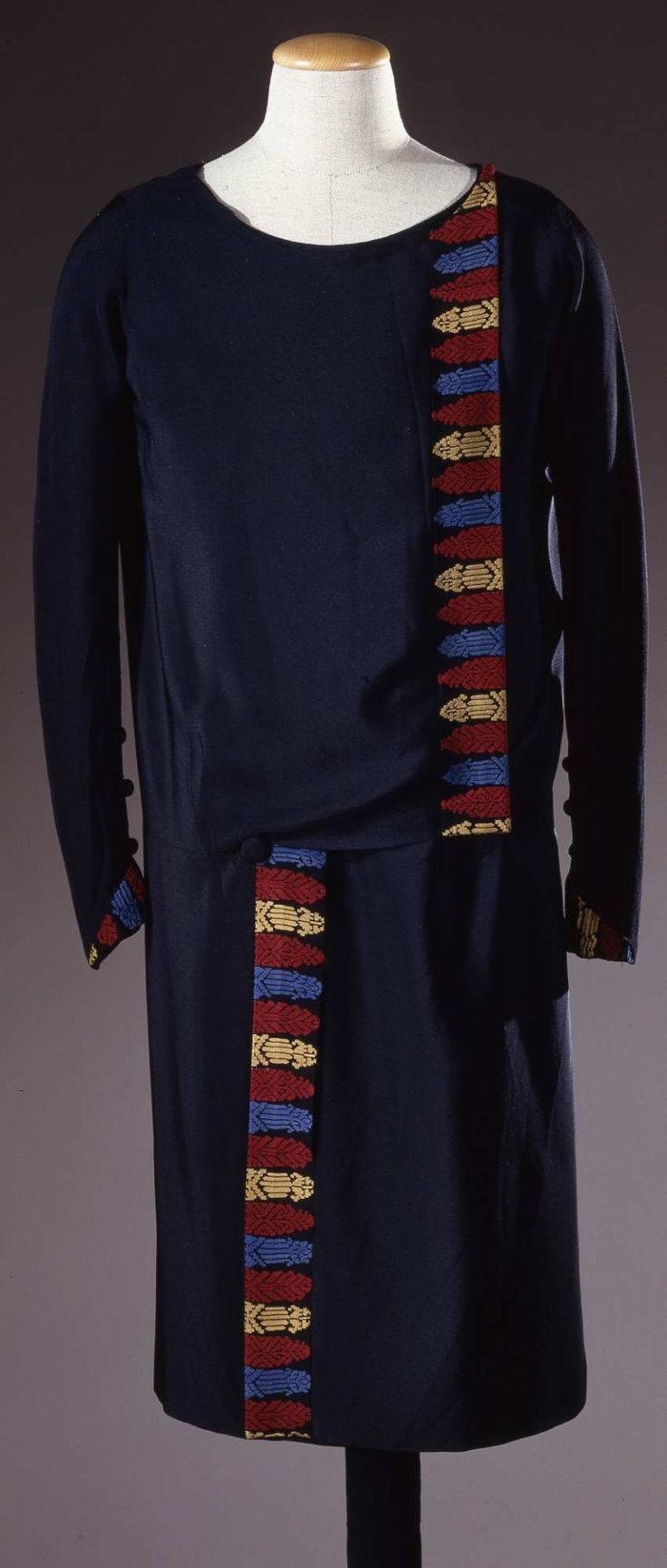 Dress 1928 Black silk crepe with a low waist and embroidered borders in burgundy, blue and yellow silk thread. It has a round neckline and sleeves closed by buttons at the wrist.  Bodice and skirt made of two asymmetrical panels. Fastened by hooks at the top of the garment and a button in the skirt  Galleria del Costume di Palazzo Pitti