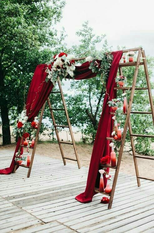 Wedding decoration - flowers and draped fabric on the arbor made of ladders would be a great ceremony backdrop