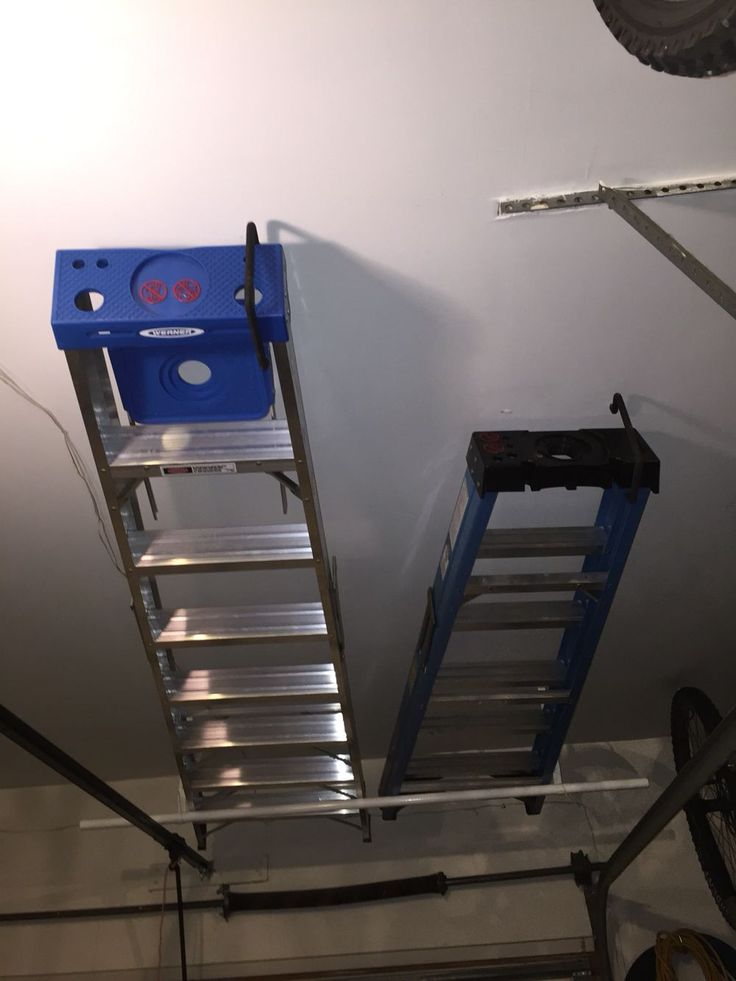 Easy ladder storage above the garage door using a clothes closet rod and ladder hook.