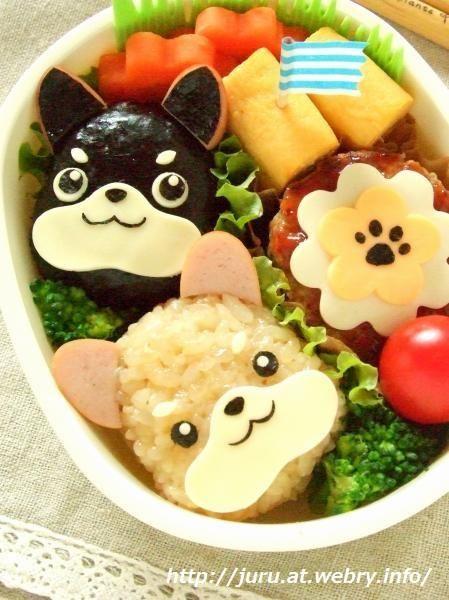 dog onigiri bento. I think it looks like a black and tan and a cream shiba inu