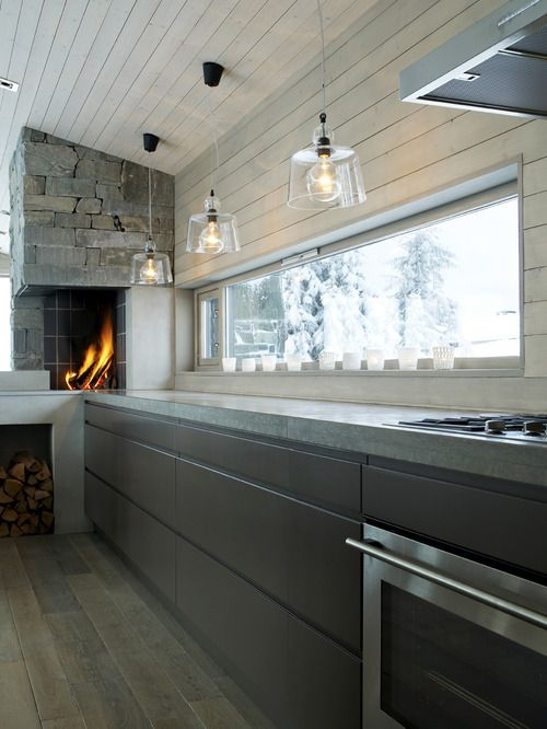 Concrete counters, dark cabinets with rustic floors and stone fireplace