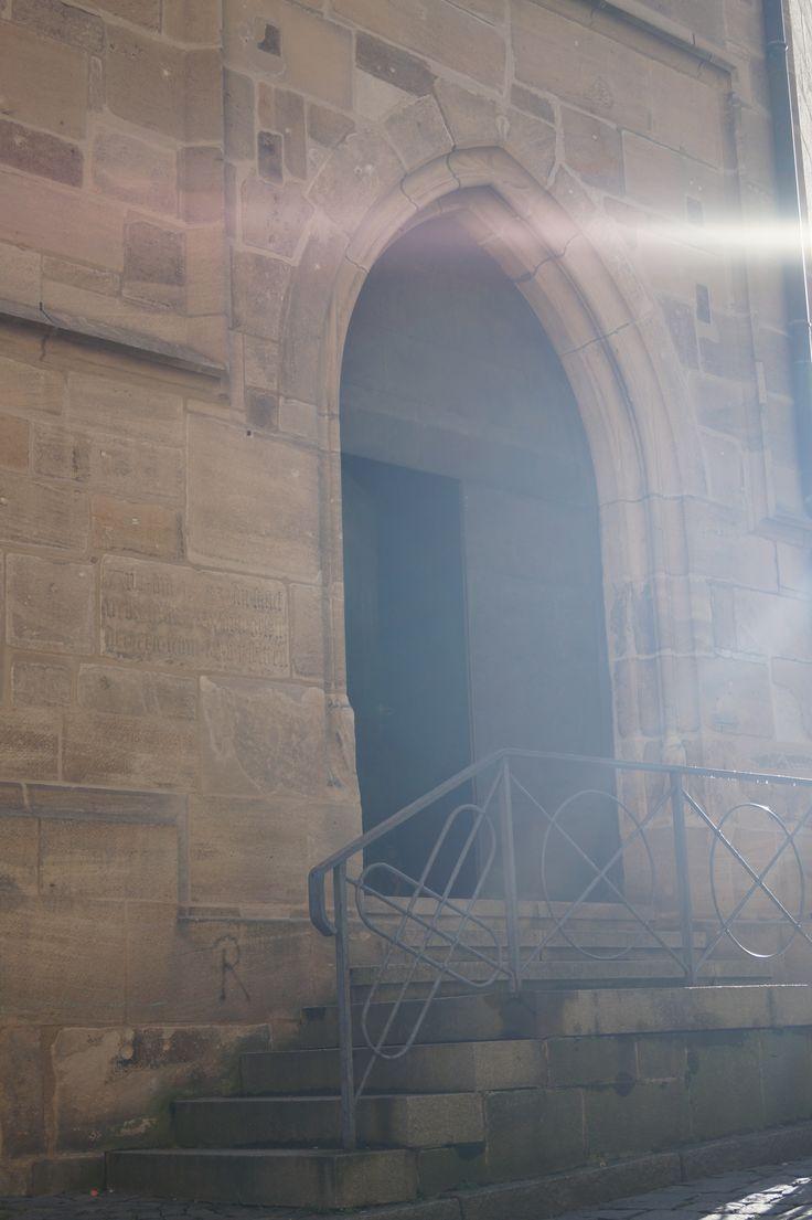 Eingang Stiftkirche mit morgendlichen Sonnenstrahlen