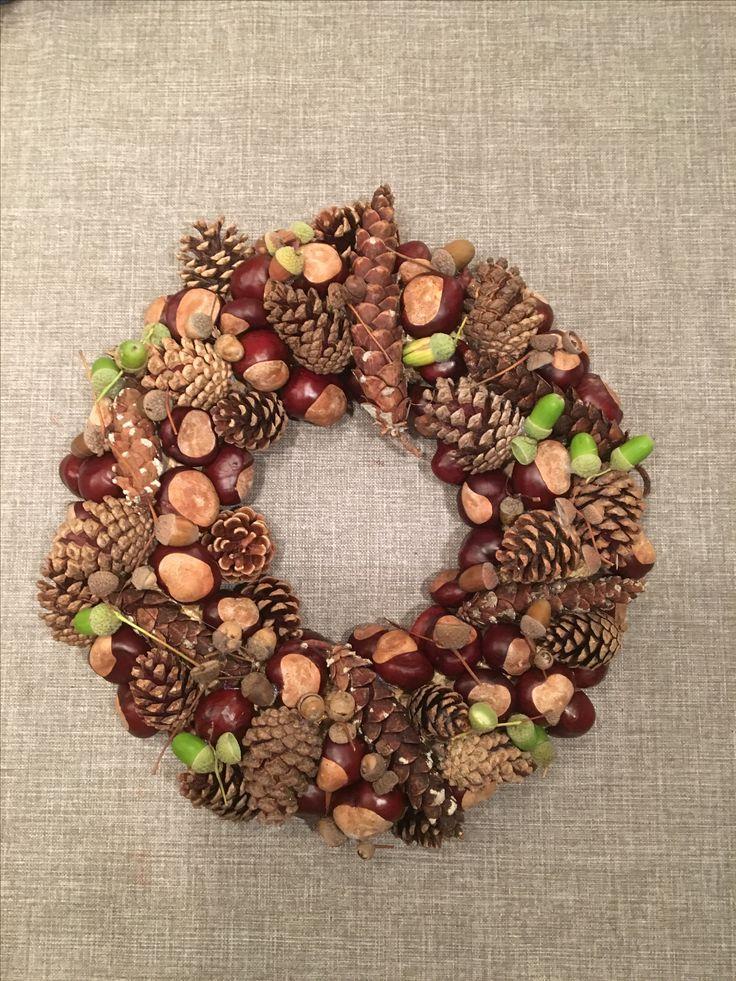 Herfstkrans gemaakt van dennenappels, kastanjes en eikels.