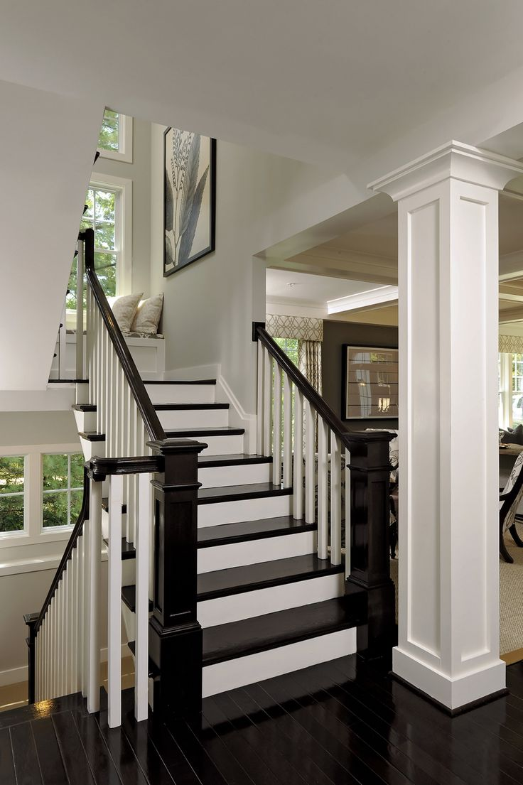 Black laquered floors on Side stair tower against white panneling= chic & modern. Opal Homes.