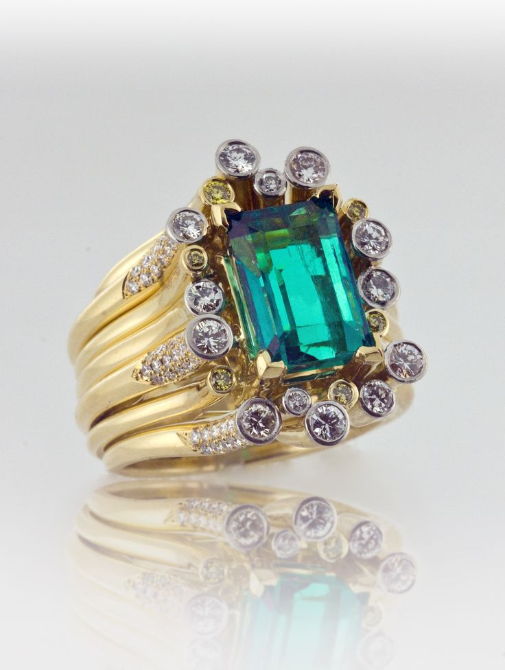 Chunky tubular emerald ring in yellow gold accented by diamonds.