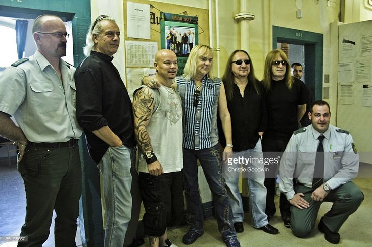 PRISON Photo of URIAH HEEP and Bernie SHAW and Mick BOX and Phil LANZON and Russell GILBROOK and Trevor BOLDER, Group portrait in a prison for a free concert L-R Prison guard, Phil Lanzon, Russell Gilbrook, Bernie Shaw, Mick Box, Trevor Bolder and prison guard