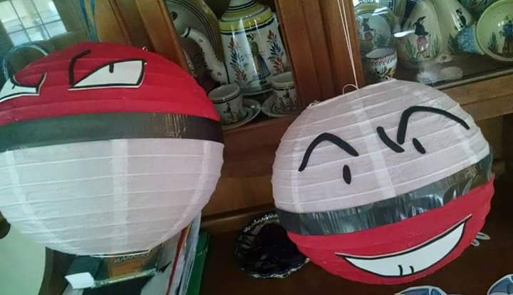 I bought plain white paper lanterns and painted half red.  Then used black self-sticking foam for faces and mouths.  I cut black duct tape in half for center line.