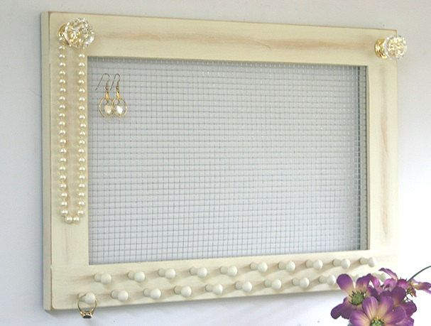 Check out our shop at www.etsy.com/shop/gardencricket/search  We handcrafted this jewelry holder that will accent beautifully in your decor. This frame is handmade out of wood, painted jersey cream and given a time worn finish. We have added 21 wooden pegs and 2 acrylic crystal knobs for necklaces and bracelets. The wire mesh and pegs make it easy to organize your jewelry. There are 2 hangers on the back for mounting to your wall or door. Overall size is 18 wide by 12 high and ...