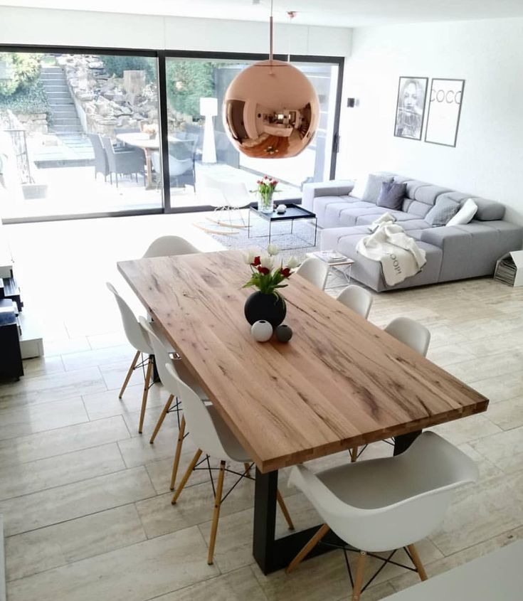 Large wooden table with black metal flat iron legs and copper lighting