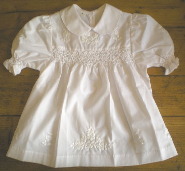 Dress for children with white embroidered motives on it.