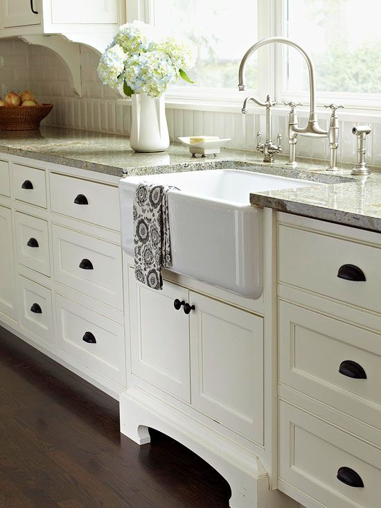 Even though the kitchen is newly remodeled, the apron-front sink, furniture-style legs, and curvaceous faucet give this kitchen an air of history. The oil-rubbed bronze cabinet pulls were inspired by dark flecks in the granite countertop and help break up the wall of white.