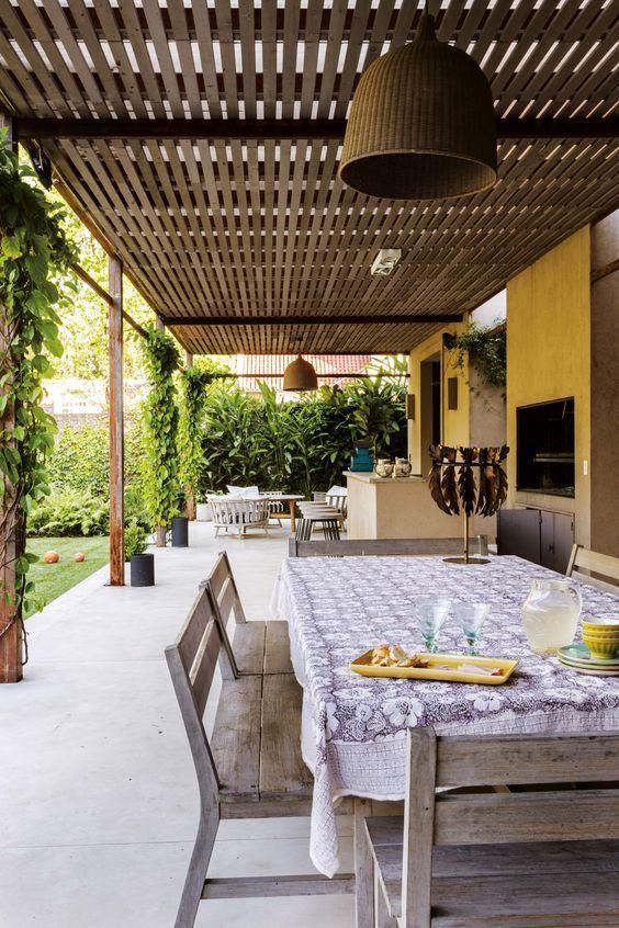 Galería de la casa de María Freytes con techo de policarbonato con listones de madera, mesa rústica y bancos del mismo material, y lámparas de techo de mimbre marrón.