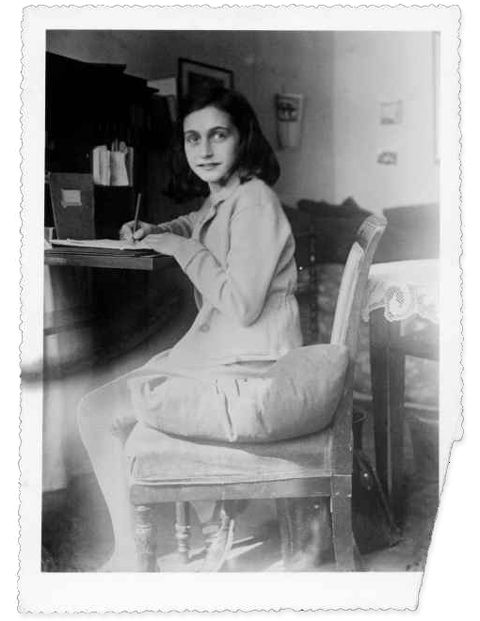 Anne Frank writing at her desk in her room in the Merwedeplein apartment, Amsterdam. Anne.. loved to write.