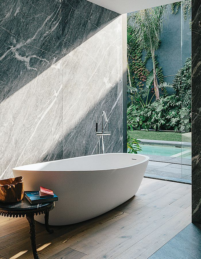 An Almond bathtub by Porcelanosa is accented by a tub filler from Hansgrohe.