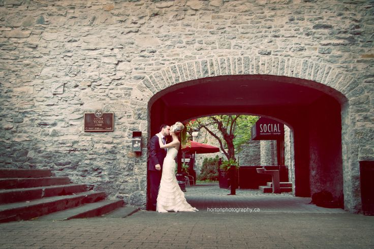 A couple sharing a kiss under an old stone archway outside the Courtyard Restaurant in Ottawa, Ontario. Photo by: Horton Photography www.hortonphotography.ca