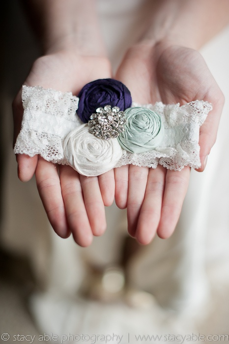 Shabby chic ivory french lace adorned with 3 dupioni hand rolled rosettes adorned with crystal brooch. A single rolled dupioni rosette garter toss is included.    Stacy Able Photography