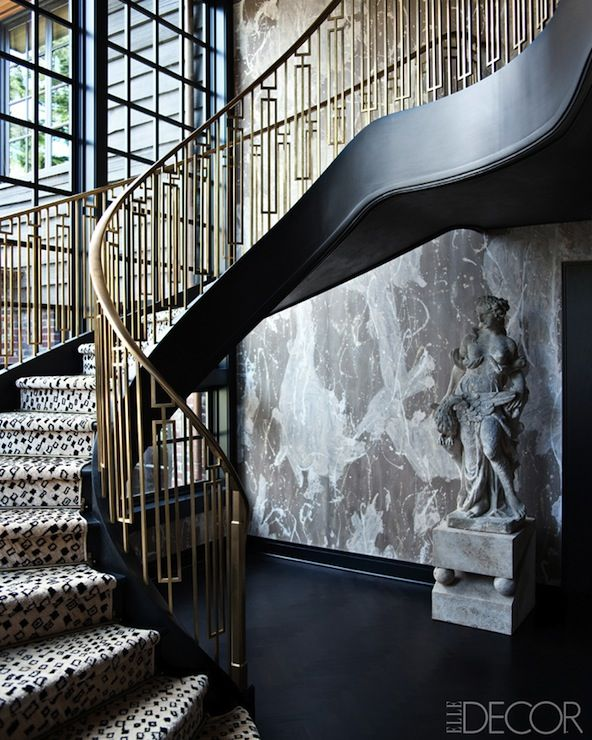 The staircase off the salon has a brass railing designed by wearstler and the wallpaper is by porter teleo interior design by kelly wearstler
