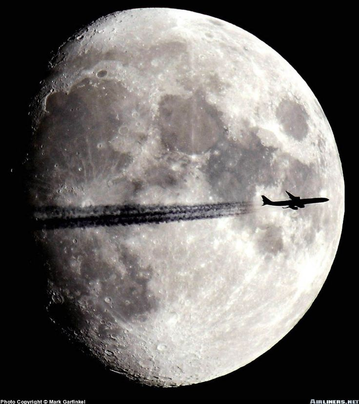 A very high jet enters the East Coast of the United States at Boston as a nearly full moon rises in the background.