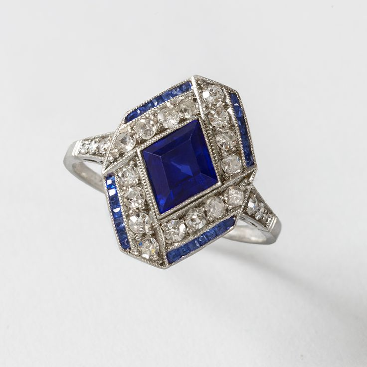 Art Deco Diamond and Sapphire Ring  An Art Deco platinum ring with blue sapphires, and diamonds. The ring has a marquise-cut blue sapphire with an approximate total weight of .75 carats, 22 old European-cut diamonds with an approximate total weight of .66 carats, and 28 calibre cut blue sapphires with an approximate total weight of .19 carats, 1920s