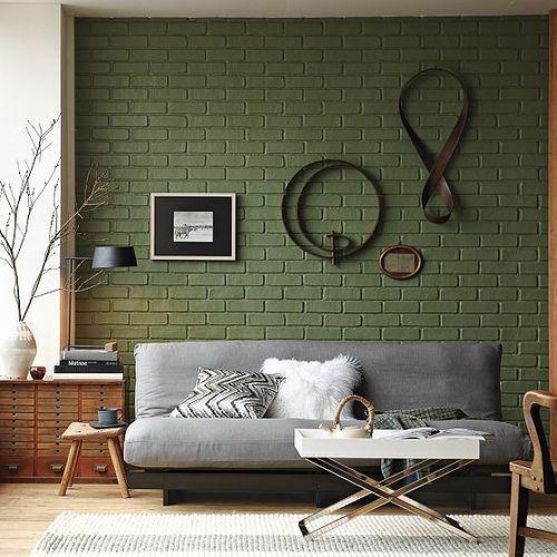 sage green brick wall and a grey sofa