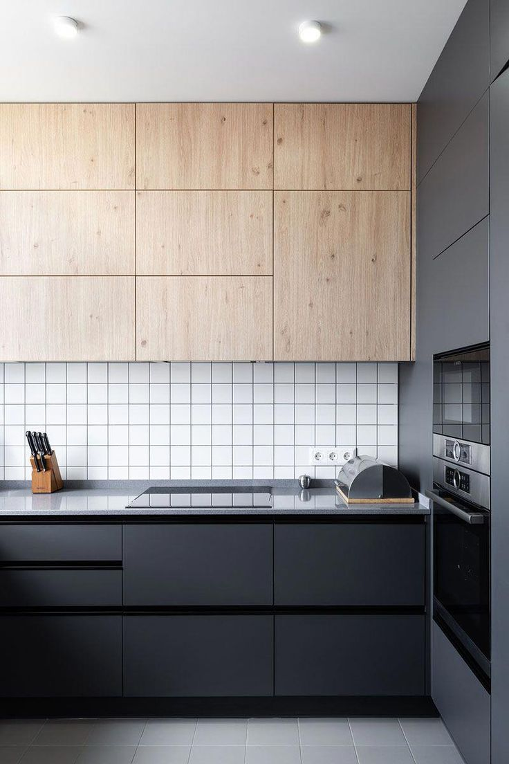 In this modern kitchen, black cabinetry contrasts the white tiles, while upper wood cabinets add a natural touch.