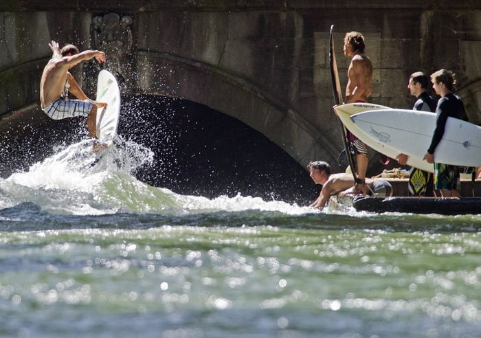 A guy surfing at the Isar river, München (Germany)