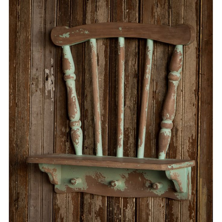 Functional and charming, this repurposed chair shelf, with its heavily distressed green painted finish, is sure to make a statement in your vintage style home.