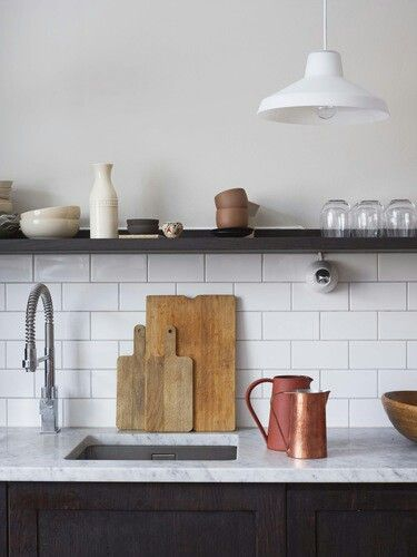 Subway tile and dark lower cabinets and floating shelf upper