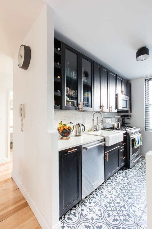 Before & After: A Crumbling 1970s Kitchen Goes Dark |  The kitchen retains its original galley shape, and is still a distinct space, but it's now much more open to the rest of the apartment. Fabio and Melina were concerned that, if they chose a strong color for the renovation, they would eventually tire of it, so instead they went with a neutral color palette.