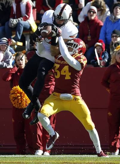 Oklahoma State 's Charlie Moore (17) catches a touchdown pass as Iowa State's Nigel Tribune defends during the college football game between the Oklahoma State University (OSU) and Iowa State University (ISU)