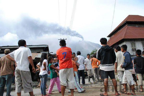 TERBIASA-Sejumlah warga Desa Gurukinayan yang berjarak 2 kilometer dari Gunung Sinabung mulai terbiasa menyaksikan Sinabung saat erupsi, Rab...