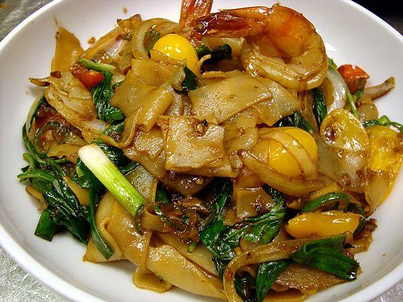 Jet Tila's Drunken Noodles Recipe- 3 Tbsp black soy sauce, 1 Tbsp sweet soy sauce, 1 Tbsp oyster sauce, 2 Tbsp fish sauce, 3 Tbsp peanut oil, 3 garlic cloves, 2 eggs, 1/3 lb chicken/beef/pork/shrimp, 1/2 white onion, 4 cups fresh rice noodles, 1 cup Thai basil leaves, 1/2 med tomato, 1/2 tsp white pepper.