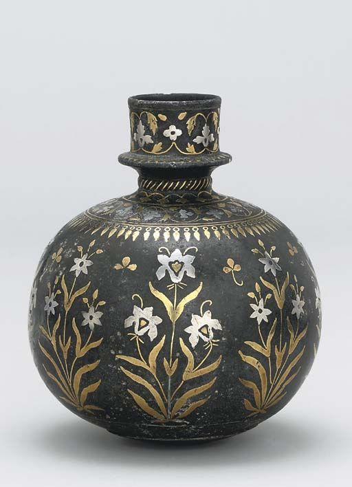 """""""A BIDRI BRASS AND SILVER INLAID SPHERICAL HOOKAH BASE, BIDAR, DECCAN, CENTRAL INDIA, LATE 17TH OR EARLY 18TH CENTURY. With cylindrical mouth, the sides with a broad band of large alternating inlaid irises and narcissi, arcaded band below, meandering floral and pendant bands on the shoulder, the mouth with a similar meandering floral tendril, slight damage to inlay, one area of restoration, base with later copper disc. 7 5/8in"""