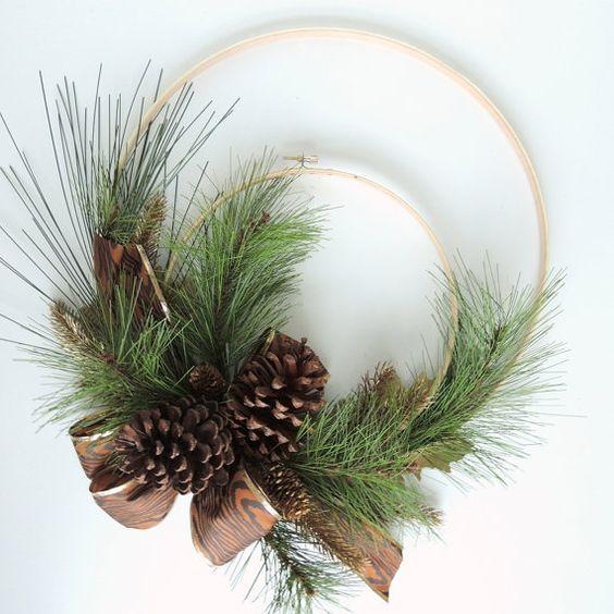 Ghirlanda natalizia realizzata con du cerchietti di legno concentrici tenuti insieme da una decorazione laterale di rami di abete, pigne e un nastro